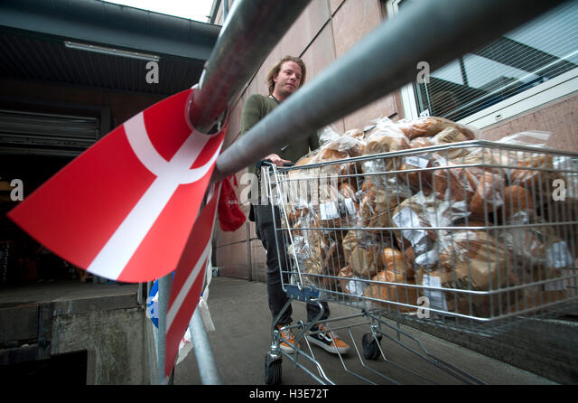 Volunteer for Wefood seen here collecting bread past its 'best buy' date from a supermarket chain in Copenhagen - Stock Image