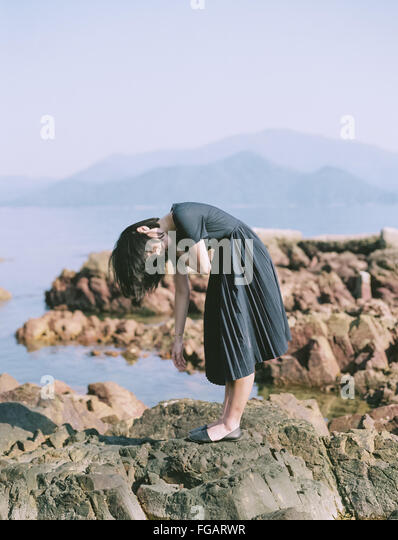 Woman Bending While Standing On Rock At Seaside - Stock Image