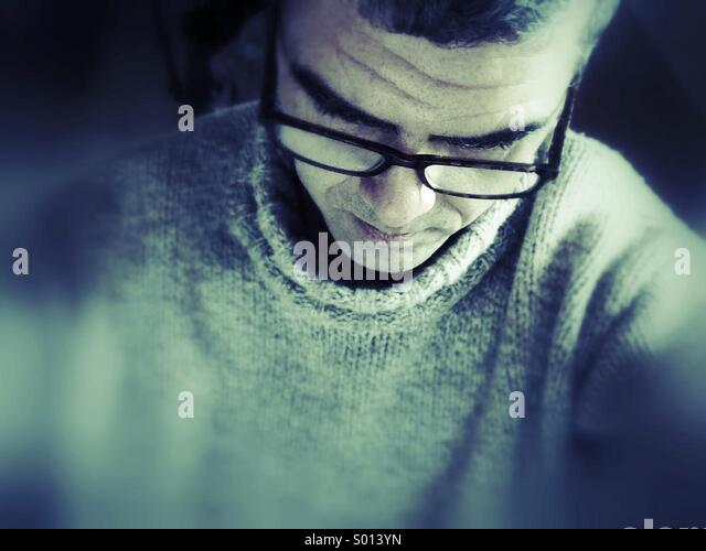 Man with glasses reading. - Stock Image