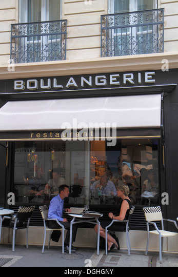 Paris France Europe French 8th arrondissement boulangerie cafe restaurant chairs tables couple man woman alfresco - Stock Image