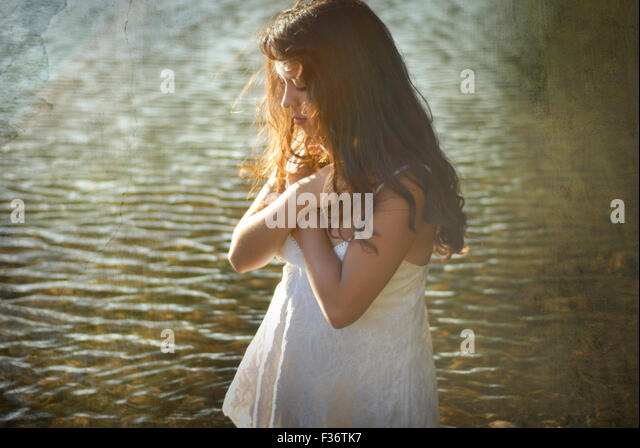 girl cross arms in the water river summer white dress long hair - Stock Image