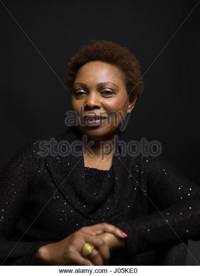 Portrait smiling African American woman against black background - Stock Image