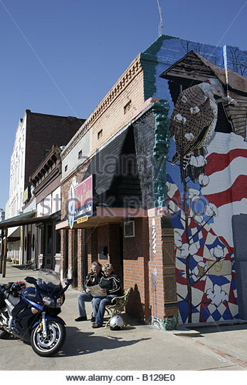 Alabama Union Springs Prairie Street man woman couple motorcycle bench read barbershop building preservation downtown - Stock Image