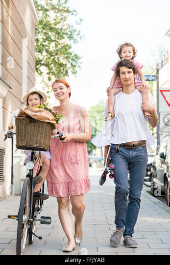 Family with two children walking in city - Stock Image