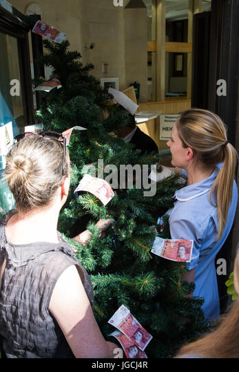 London, UK. 5th July, 2017. A nurse attempts to deliver a magic money tree to the Department of Health during a - Stock Image