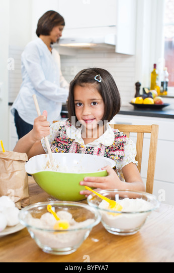 Portrait of girl baking in kitchen with mother in background - Stock-Bilder
