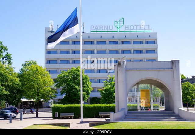 Estonian flag on the main square of Pärnu with the independence monument and hotel Pärnu in the background - Stock Image