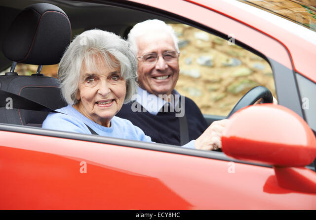 Portrait Of Smiling Senior Couple Out For Drive In Car - Stock Image