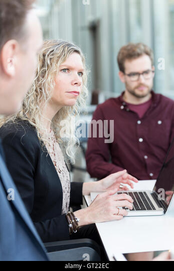 Businesswoman using laptop while sitting with colleagues at office - Stock-Bilder