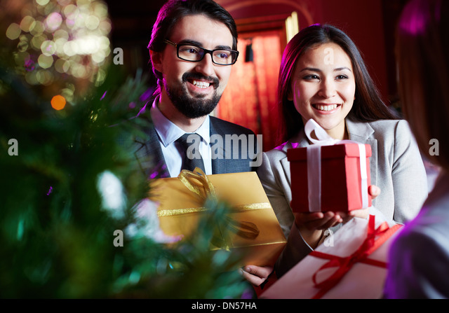 Portrait of joyful colleagues giving xmas presents to their associate - Stock Image