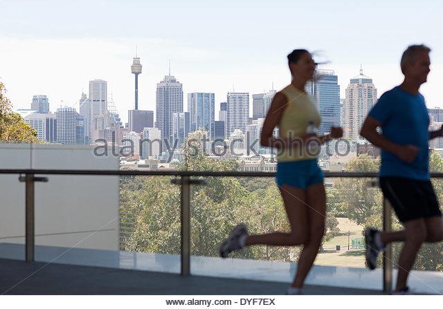 Couple running in urban setting - Stock-Bilder