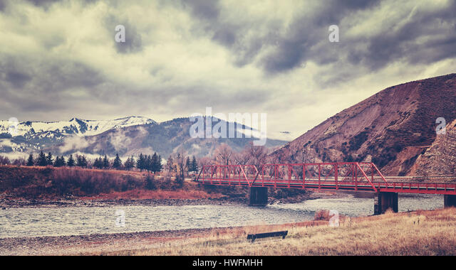 Red bridge in Rocky Mountains, color toning applied, Colorado, USA. - Stock Image