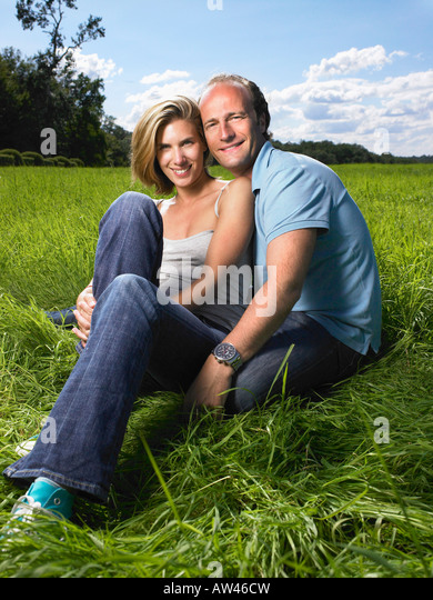 Couple sitting in a field. - Stock Image