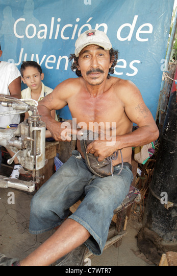 Managua Nicaragua Mercado Oriental market marketplace shopping stall shed shoe repair Hispanic man boy middle age - Stock Image