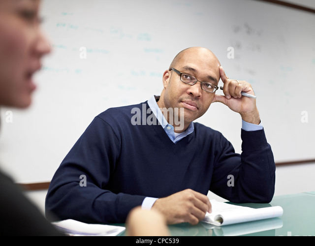 A man looks at a woman during a conference room meeting - Stock Image