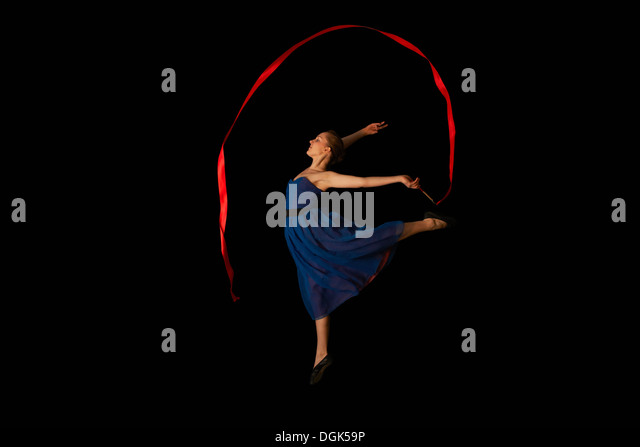 Dancer with ribbon on black background - Stock Image