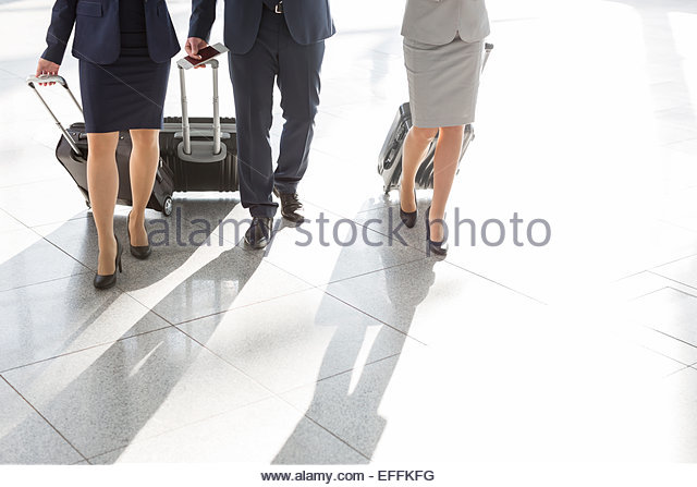 Low section of businesspeople walking at the airport - Stock Image