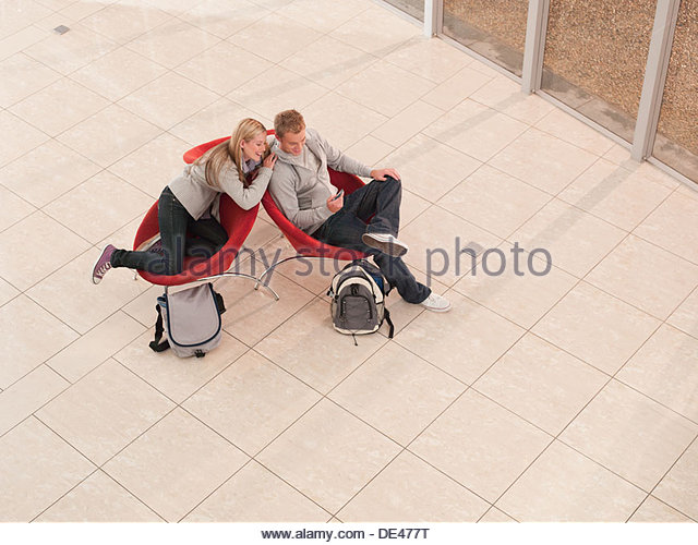College friends view cell phone in lobby - Stock Image