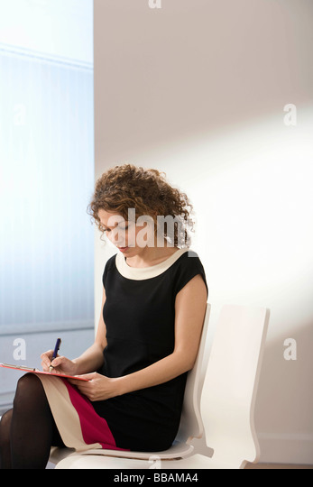 A female filling in a form - Stock Image