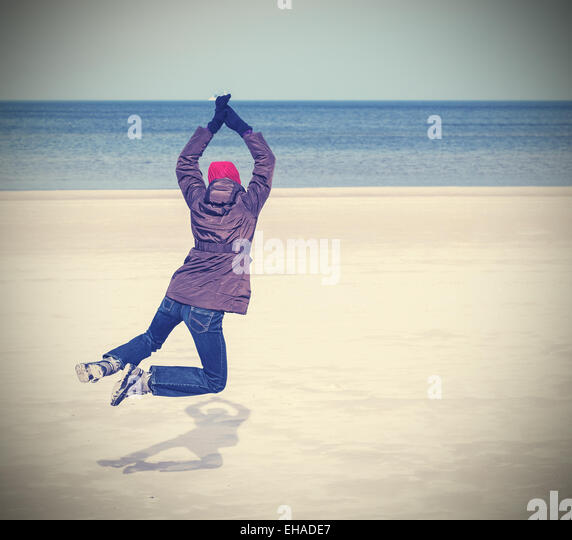 Retro filtered photo of woman jumping on beach, winter active lifestyle concept, space for text. - Stock-Bilder