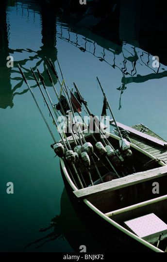 A small fishing boat with marker bouys in a harbour with reflections - Stock Image