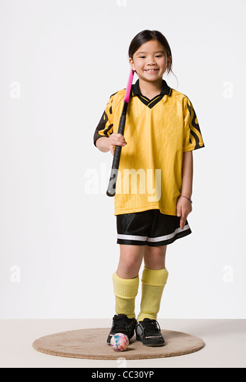 Portrait of smiling girl (8-9) wearing field hockey costume, studio shot - Stock Image