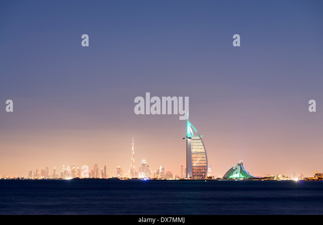 Night skyline across sea to luxury Burj al Arab hotel and city of Dubai with Burj Khalifa tower in distance United - Stock Image