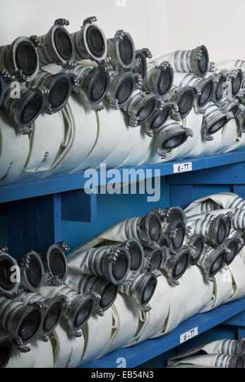 Fire hoses are stored on a shelf - Stock Image