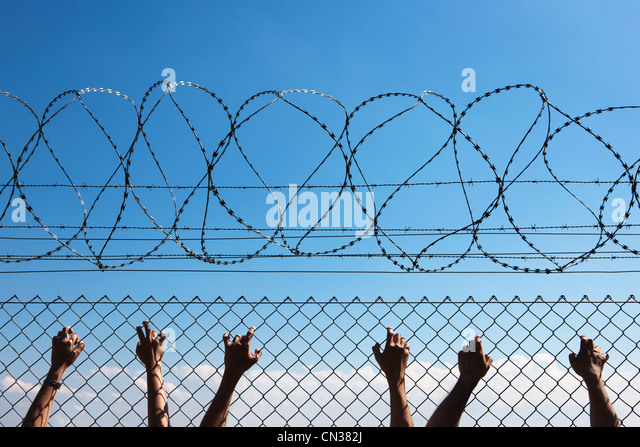 Three people's hands on wire fence - Stock Image