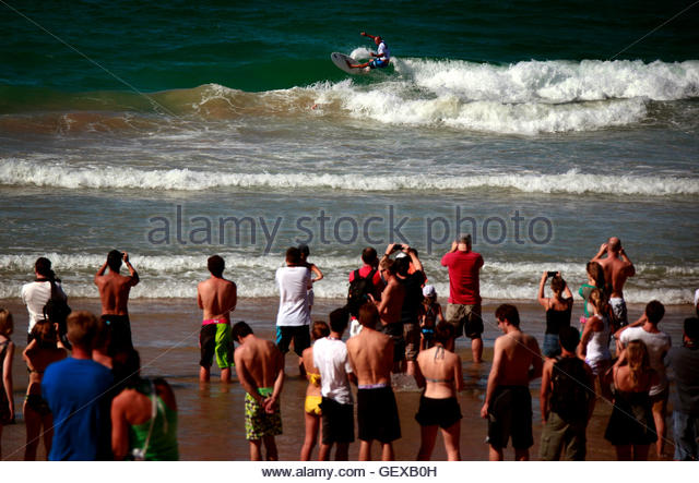 Crowd watch 11-time world surfing champion Kelly Slater of the U.S. ride a wave during a promotional event at Sydney's - Stock Image