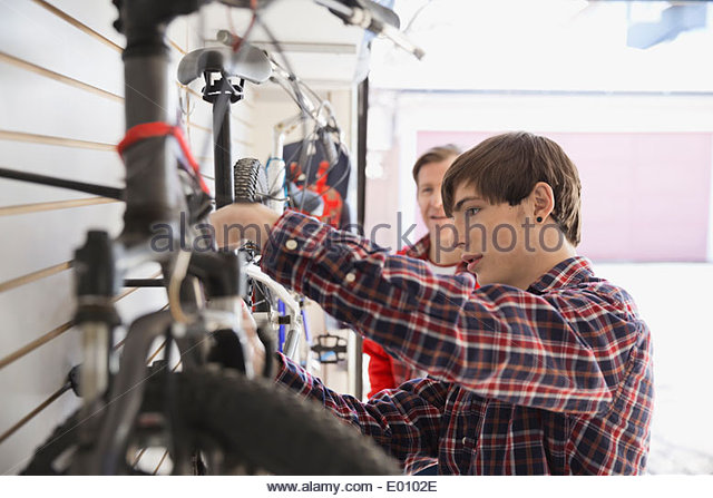 Father and son repairing bicycle in garage - Stock Image