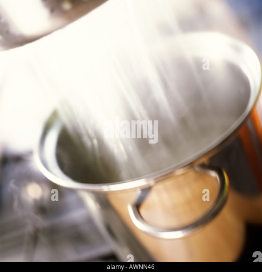 Close-up of water draining into pot on stove - Stock Image