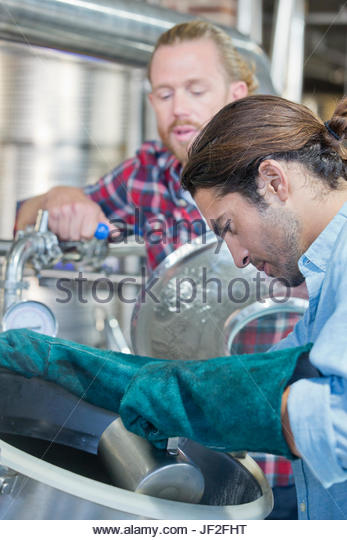 Brewery Workers Checking Fermentation Process In Steel Vat - Stock Image