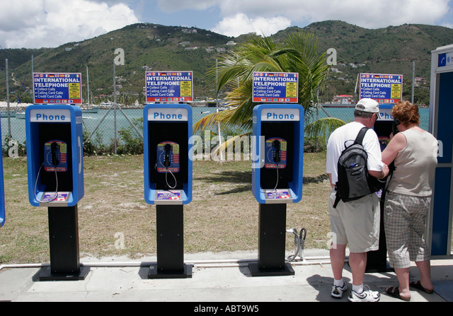 BVI Tortola Road Town pay phone international telephone couple - Stock Image