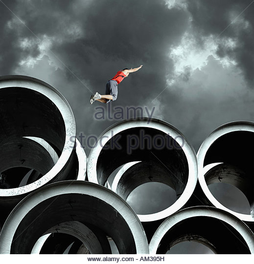 Long jumper on large cylinders - Stock Image