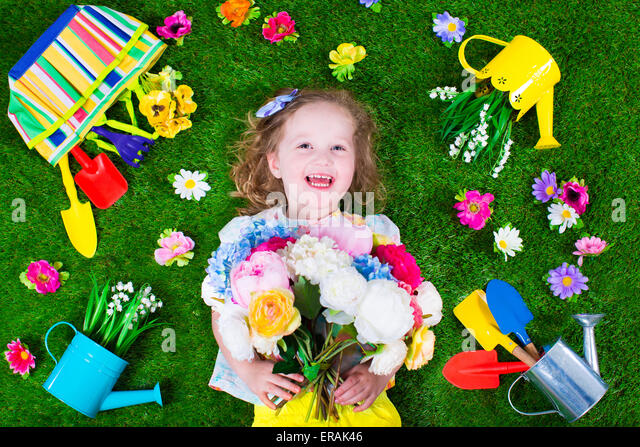 Kids gardening. Children with garden tools. Child with watering can and shovel. Little kid watering flowers. - Stock Image