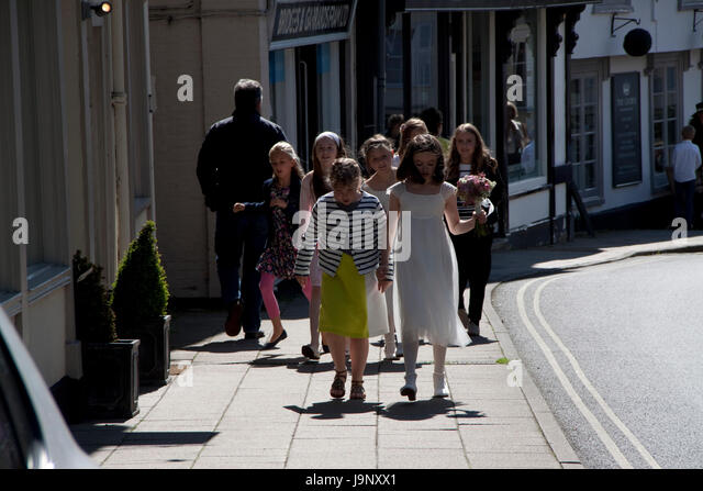 Young bridesmaids carrying posies and with friends walking in the street - Stock Image