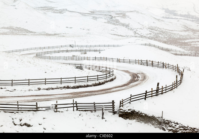 Snow on winding road in Edale, Peak District National Park, Derbyshire, England, United Kingdom, Europe - Stock Image