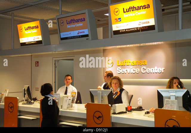 Germany Frankfurt am Main Airport FRA terminal gate area concourse Lufthansa service center centre man woman employee - Stock Image