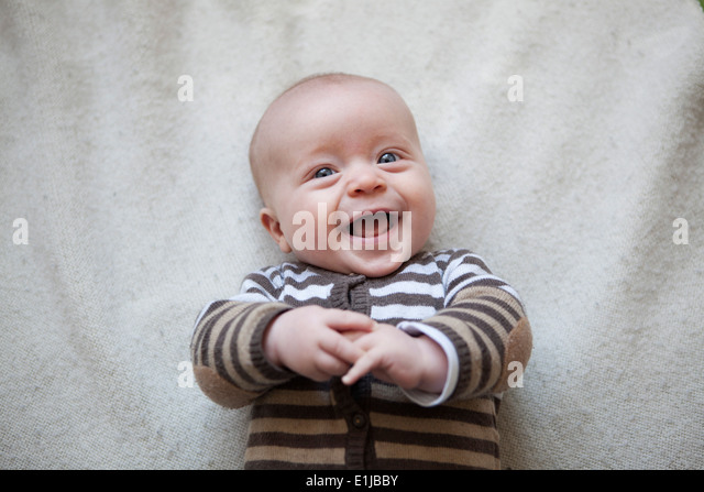 Portrait of laughing baby boy lying on blanket, view from above - Stock Image