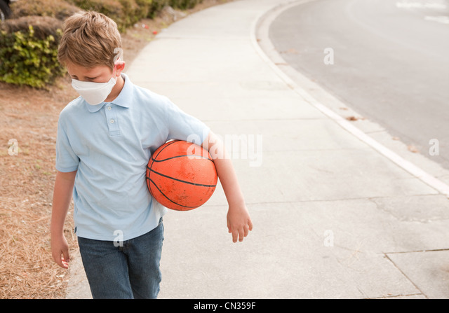Boy wearing dust mask holding basketball - Stock Image
