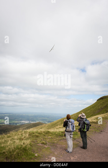 Watching a glider fly near the summit of Pen-y-Fan in the Brecon beacons, Wales. - Stock Image