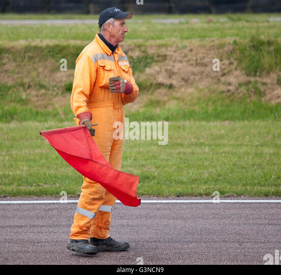 Track marshal with red flag at a motor sport event. - Stock Image