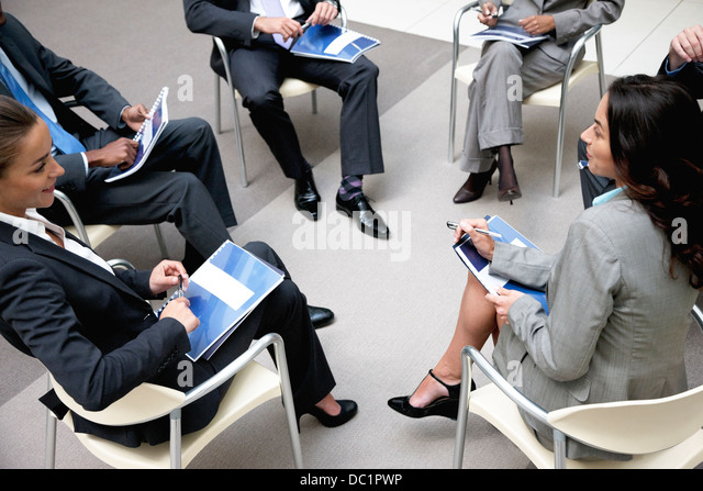 High angle view of business people meeting in circle - Stock Image