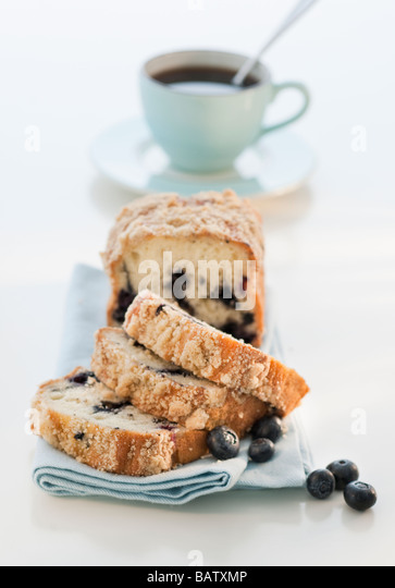 Blueberry cake with coffee cup in background - Stock Image