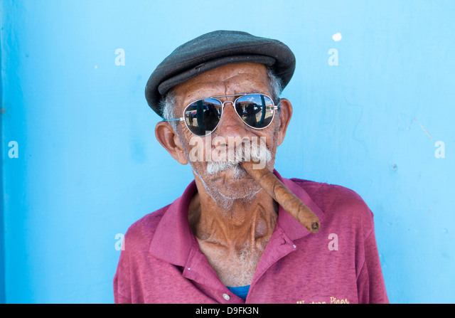 Old man wearing sunglasses and flat cap, smoking big Cuban cigar, Vinales, Pinar Del Rio Province, Cuba, West Indies - Stock Image