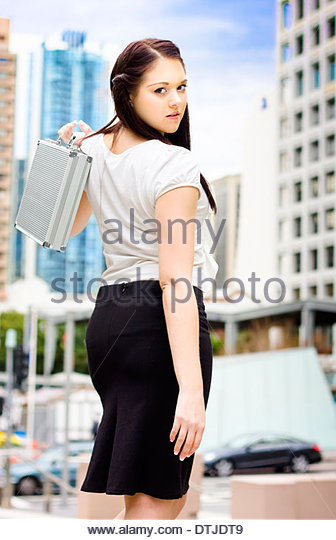 Modern And New Age Professional Business Woman Walking With Metal Briefcase On A Contemporary Urban Road When On - Stock Image