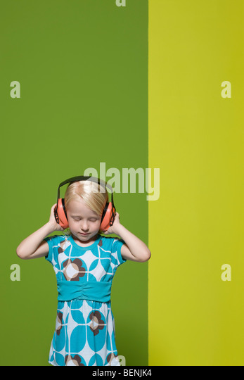 Little girl with eyes closed wearing protective headphones - Stock Image