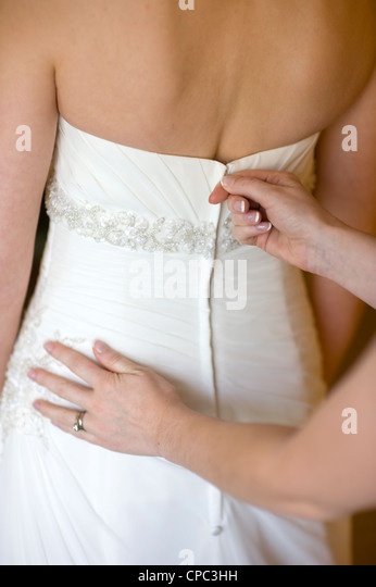 bridesmaid zips up the wedding dress of the bride - Stock Image