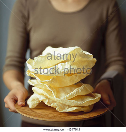 Woman serving poppadams on wooden plate - Stock-Bilder